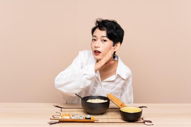 Jeune femme asiatique dans une table avec bol de nouilles et sushi chuchoter quelque chose