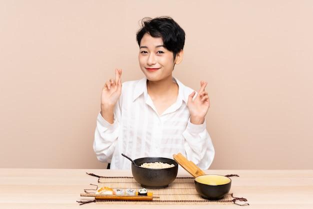 Jeune, femme asiatique, dans, a, table, à, bol, de, nouilles, et, sushi, à, doigts, croisement