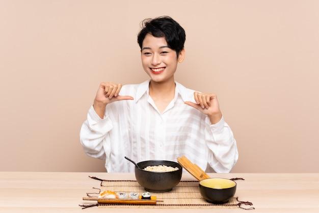 Jeune femme asiatique dans une table avec bol de nouilles et sushi fier et satisfait de lui-même
