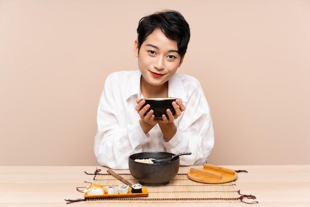 Jeune femme asiatique dans une table avec bol de nouilles et sushi