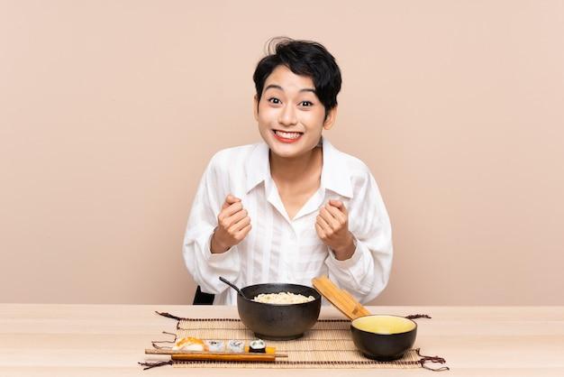Jeune femme asiatique dans une table avec bol de nouilles et sushis célébrant une victoire