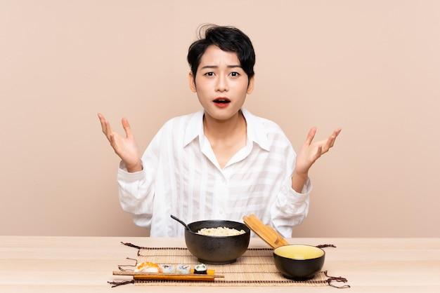 Jeune femme asiatique dans une table avec bol de nouilles et sushis avec expression faciale surprise