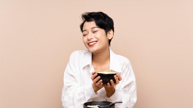 Jeune femme asiatique dans une table avec bol de nouilles