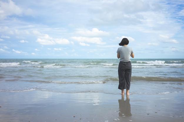 Jeune femme asiatique debout face à la mer. se sentir vraiment seul, mer déchirée comme