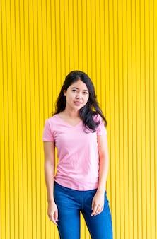 Jeune femme asiatique, debout, sur, mur jaune