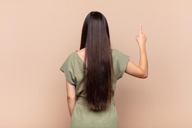 Jeune femme asiatique debout et pointant vers l'objet sur l'espace de copie, vue arrière