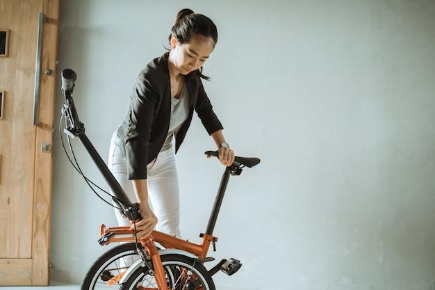 Jeune Femme Asiatique Debout Sur Le Salon Lorsqu'il Est Ouvert Plier Son Vélo Pliant Photo Premium