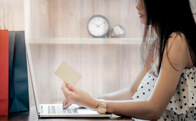 Jeune femme asiatique détenant une carte de crédit et utilisant un ordinateur portable au bureau ou à la maison.