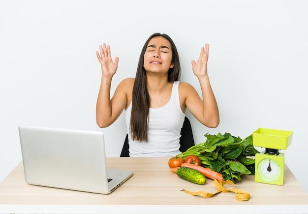 Jeune femme asiatique diététicienne isolée sur blanc criant vers le ciel, levant les yeux, frustrée.