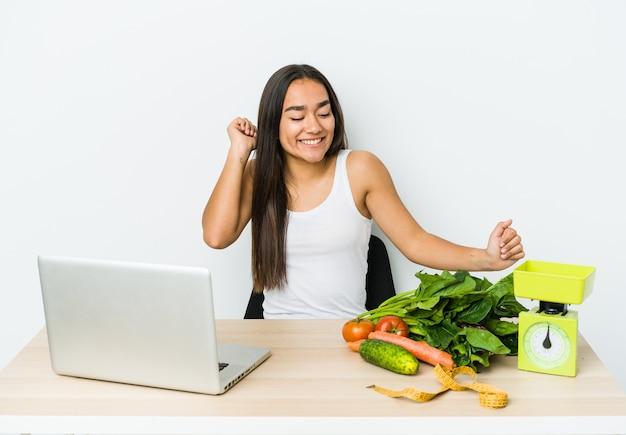 Jeune femme asiatique diététicienne isolée sur un mur blanc dansant et s'amusant