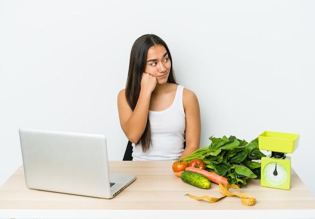 Jeune femme asiatique diététicienne isolée sur un mur blanc qui se sent triste et pensif, regardant copie espace