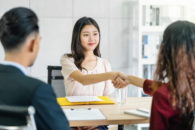 Jeune femme asiatique diplômée serrer la main avec deux managers pour accueillir