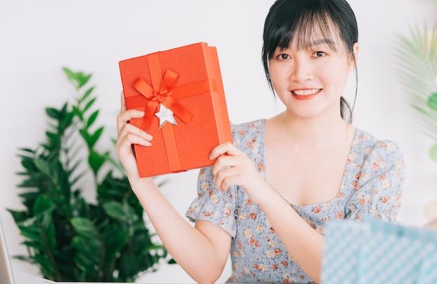 Jeune femme asiatique en direct pour offrir des cadeaux au public en regardant son flux sur les plateformes de réseaux sociaux