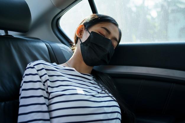 Jeune femme asiatique dormant sur les sièges arrière de la voiture, après être épuisée par le tourisme forestier.