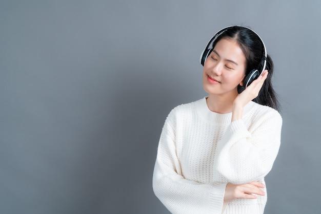 Jeune femme asiatique à l'écoute et profiter de la musique avec des écouteurs