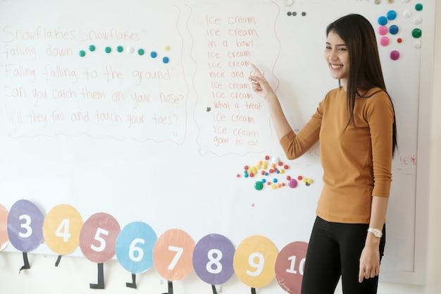 Jeune femme asiatique enseignant l'enseignement des enfants anglais