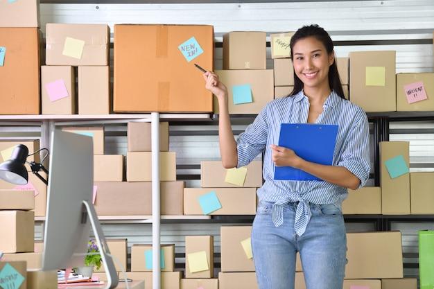 Jeune femme asiatique entrepreneur chef d'entreprise travaillant à la maison pour faire des achats en ligne et préparer le package de produit