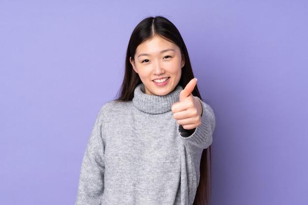Jeune femme asiatique sur un espace isolé avec les pouces vers le haut parce que quelque chose de bien s'est produit