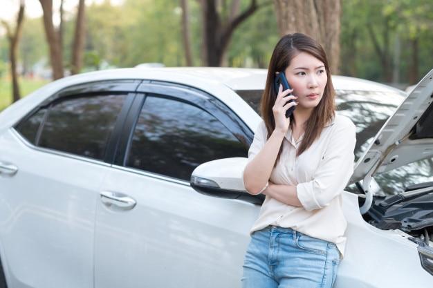 Jeune femme asiatique essaie d'appeler de l'aide pour sa voiture en panne
