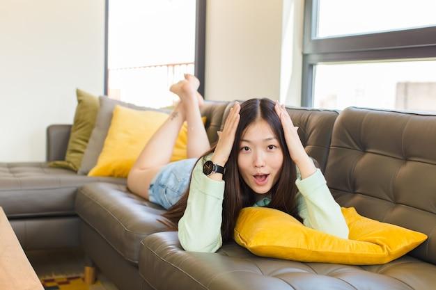 Jeune femme asiatique à excité et surpris, bouche bée avec les deux mains sur la tête, se sentant comme un heureux gagnant