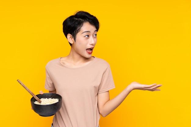 Jeune femme asiatique avec une expression faciale surprise tout en tenant un bol de nouilles avec des baguettes