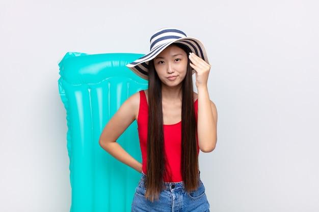Jeune femme asiatique faisant capice ou geste d'argent, vous disant de payer vos dettes!. concept d'été