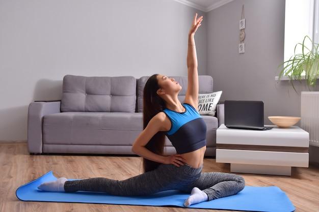 Jeune femme asiatique faisant du yoga à la maison.
