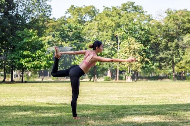 Jeune femme asiatique faisant du yoga le matin au parc
