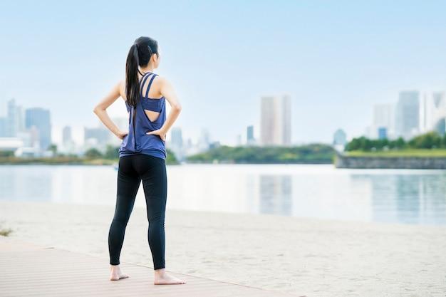Jeune femme asiatique faisant du yoga sur la plage de la ville