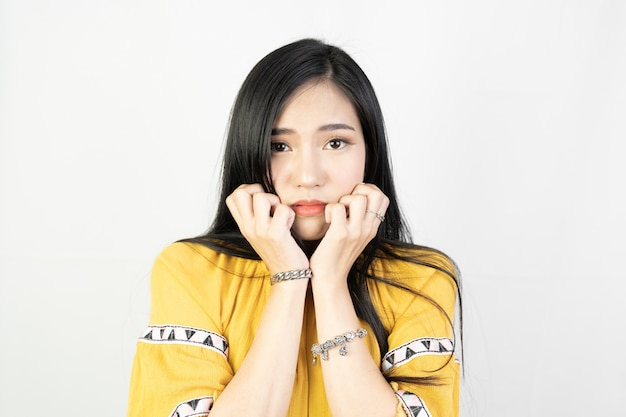 Jeune femme asiatique faisant une expression timide sur blanc