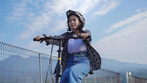Une jeune femme asiatique fait du vélo pour se rendre au travail, elle est heureuse et en sécurité