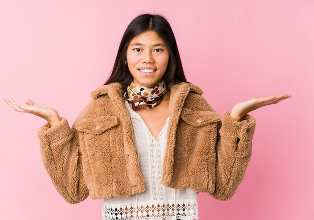 La jeune femme asiatique fait de l'échelle avec les bras, se sent heureuse et confiante.