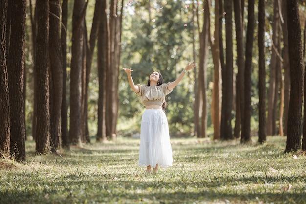 Jeune femme asiatique fille très heureuse et souriante dans le jardin et tenant mains