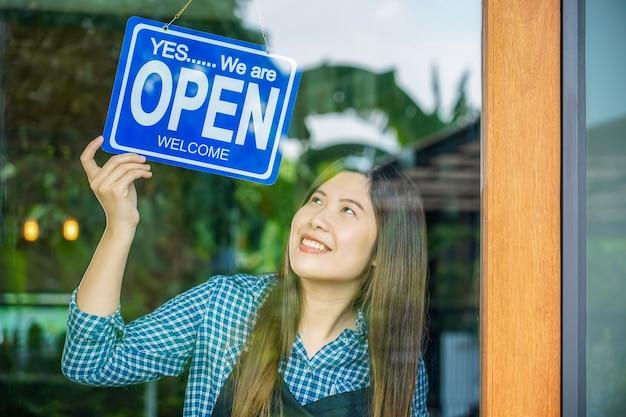 Jeune femme asiatique fixant un panneau ouvert à la boutique des lunettes pour accueillir le client