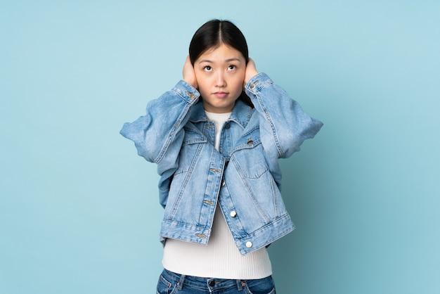 Jeune femme asiatique frustrée et couvrant les oreilles