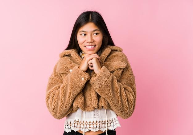 Une jeune femme asiatique garde les mains sous le menton, regarde joyeusement de côté.