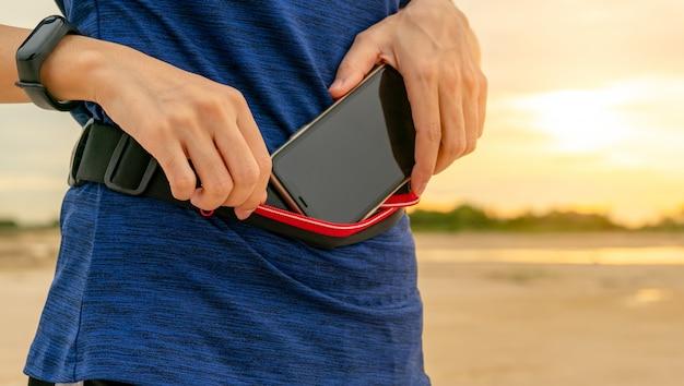 Jeune femme asiatique garder le smartphone dans le sac de taille avant d'exécuter un exercice cardio le matin.