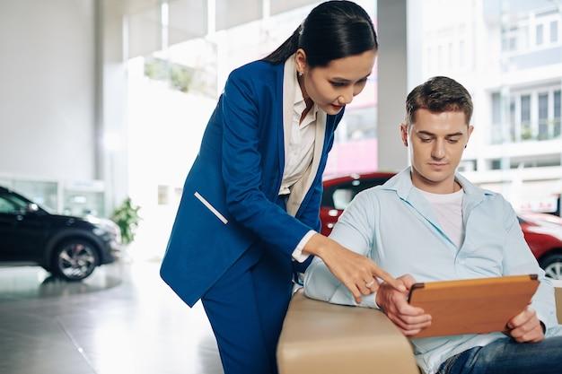 Jeune femme asiatique gestionnaire de concessionnaire automobile aidant le client à trouver la bonne voiture dans le catalogue en ligne sur ordinateur tablette