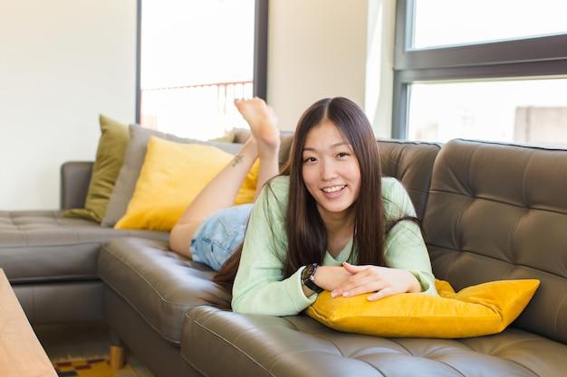 Jeune femme asiatique avec un grand sourire amical et insouciant, à la recherche de positif, détendu et heureux, effrayant