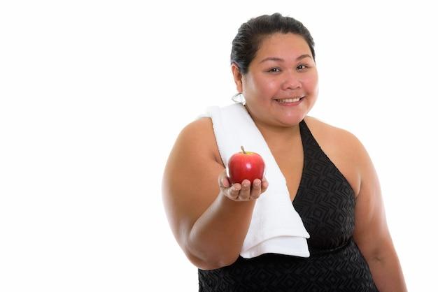 Jeune femme asiatique grasse heureuse souriant tout en tenant une pomme rouge