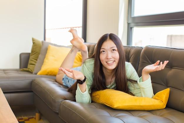 Jeune femme asiatique haussant les épaules avec une expression stupide, folle, confuse, perplexe, se sentant agacée et désemparée