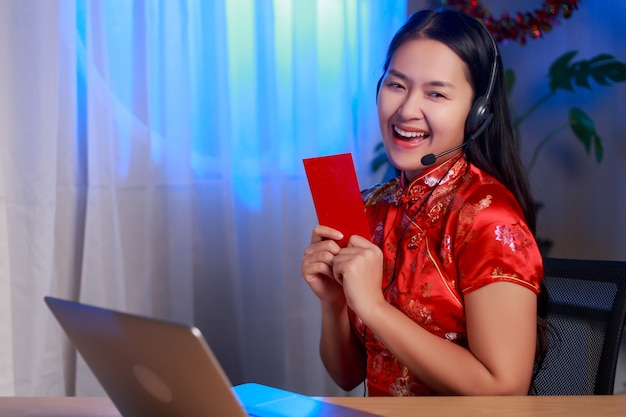 Jeune femme asiatique heureuse beauté portant une robe de tradition chinoise assis devant un ordinateur portable tenant une enveloppe rouge