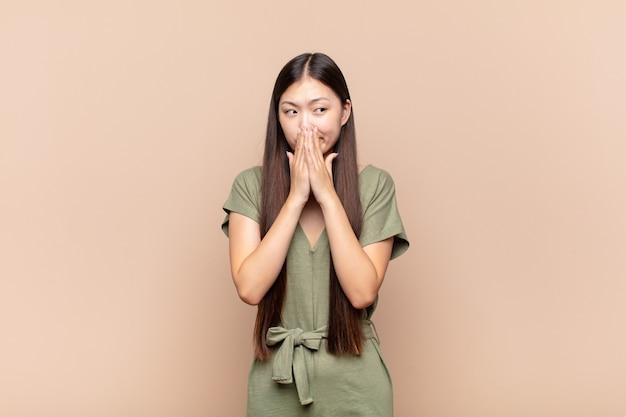 Jeune femme asiatique heureuse et excitée, surprise et étonnée couvrant la bouche avec les mains, gloussant avec une expression mignonne