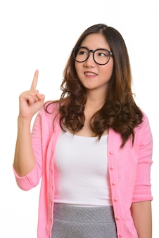 Jeune femme asiatique heureuse pointant le doigt vers le haut tout en pensant isolé contre blanc