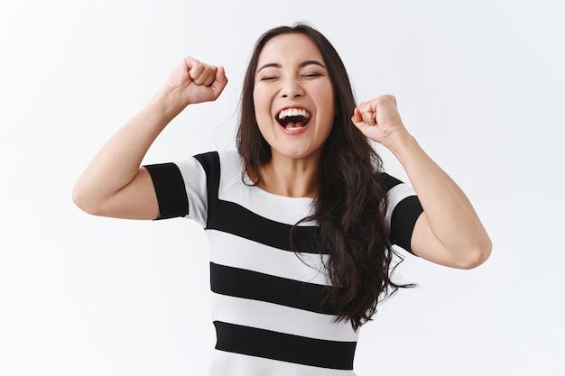 Jeune femme asiatique heureuse et soulagée en t-shirt rayé levant les mains, pompe à poing comme un champion, se sentant chanceuse et optimiste en gagnant, triomphant en criant ouais, célébrant la victoire
