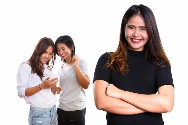 Jeune femme asiatique heureuse souriant avec les bras croisés avec deux amis heureux à l'arrière à l'aide de téléphone mobile ensemble