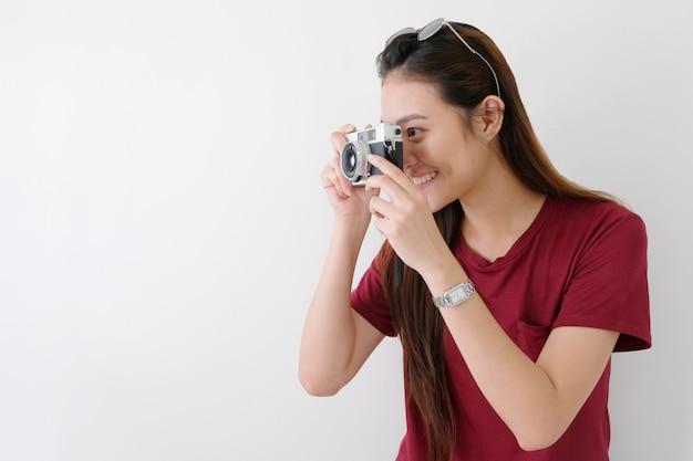 Jeune femme asiatique heureuse touristique tenant la caméra debout, fille de voyageur asiatique souriant tout en tenant la caméra vintage en vacances