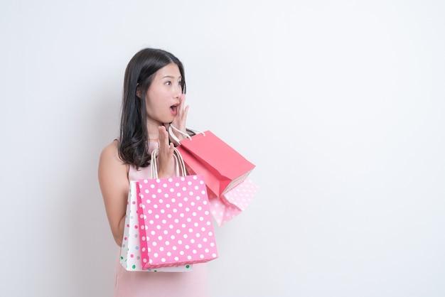 Jeune femme asiatique heureux souriant tenant un sac à provisions en robe rose sur blanc