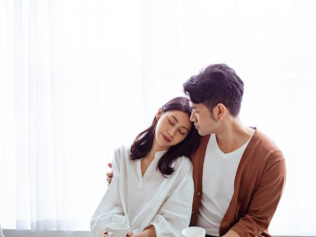 Jeune femme asiatique et homme à la maison avec une tasse de café dans les mains.
