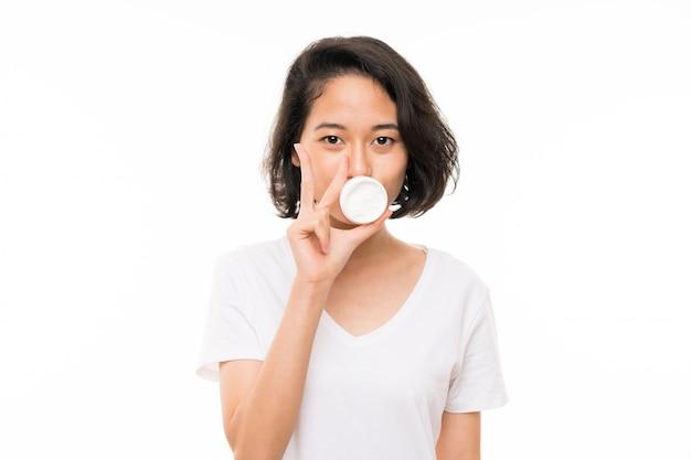 Jeune femme asiatique sur isolé avec crème hydratante